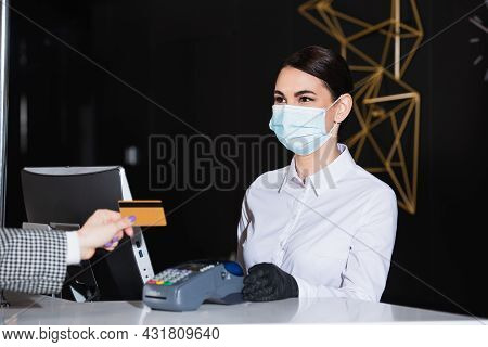 Receptionist In Latex Gloves And Medical Mask Holding Payment Terminal Near Guest With Credit Card