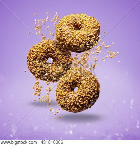 Flying Chocolate Donuts Sprinkled With Crunchy Peanut On Purple Background