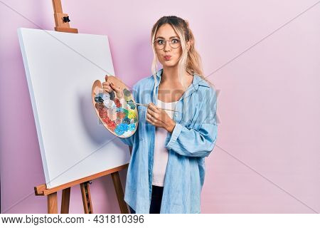 Beautiful young blonde woman standing drawing with palette by painter easel stand puffing cheeks with funny face. mouth inflated with air, catching air.