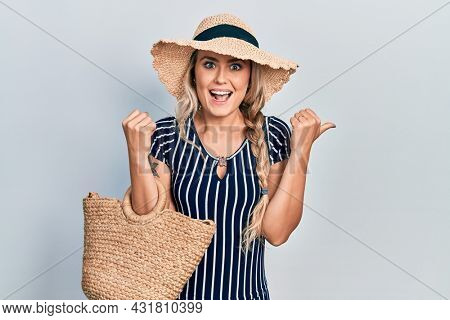 Beautiful young blonde woman wearing summer dress and wicker handbag pointing thumb up to the side smiling happy with open mouth