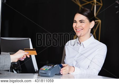 Happy Receptionist Smiling Near Guest Paying With Credit Card