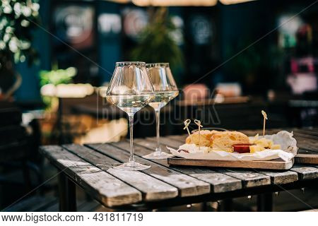 A Wooden Table In A Restaurant With A Cheese Plate, Grape, Honey Bread And White Wine. Wine Glasses