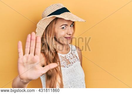 Young caucasian woman wearing summer hat doing stop sing with palm of the hand. warning expression with negative and serious gesture on the face.