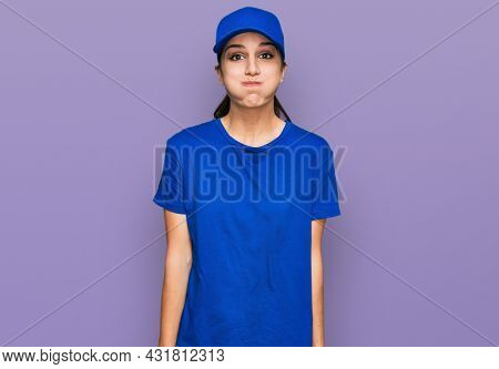 Young hispanic girl wearing delivery courier uniform puffing cheeks with funny face. mouth inflated with air, crazy expression.