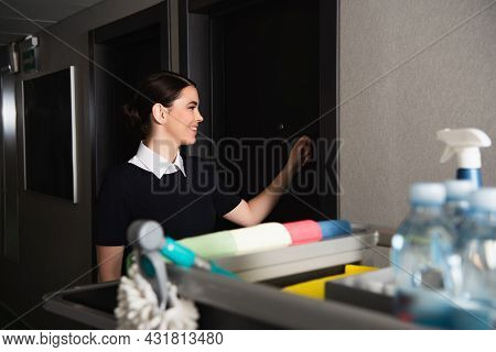 Cheerful Maid Knocking Door In Hotel Near Blurred Housekeeping Cart