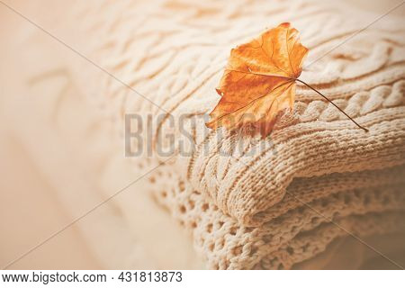 Warm Woolen Soft White Sweaters Are Stacked In A Pile, And On Top Of Them Is A Red Maple Leaf. Cold