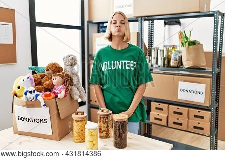Young caucasian woman wearing volunteer t shirt at donations stand puffing cheeks with funny face. mouth inflated with air, crazy expression.