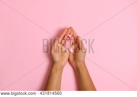 Flat Lay Of Hands Holding Pink Ribbon On Pink Background, Breast Cancer Awareness, October Pink Day,