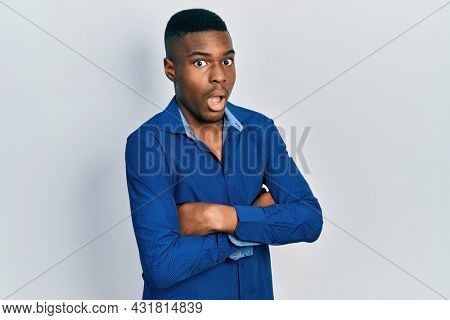 Young african american man with arms crossed gesture afraid and shocked with surprise and amazed expression, fear and excited face.