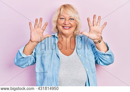 Middle age blonde woman wearing casual clothes showing and pointing up with fingers number ten while smiling confident and happy.