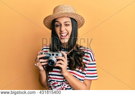 Young hispanic woman wearing summer hat holding vintage camera winking looking at the camera with sexy expression, cheerful and happy face.