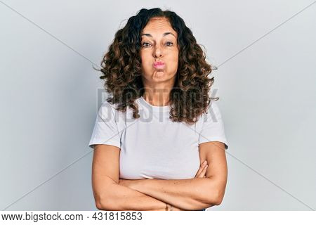 Middle age hispanic woman with arms crossed gesture puffing cheeks with funny face. mouth inflated with air, catching air.
