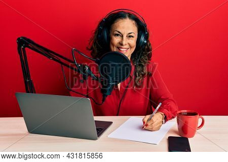 Beautiful middle age woman working at radio studio looking positive and happy standing and smiling with a confident smile showing teeth