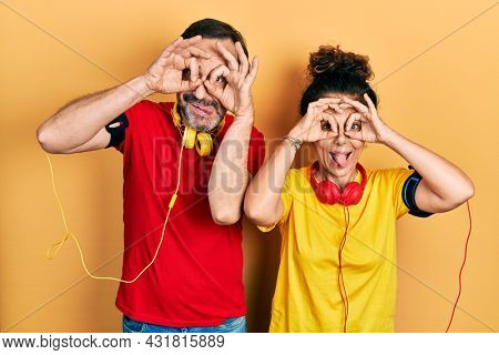 Middle age couple of hispanic woman and man wearing sportswear and arm band doing ok gesture like binoculars sticking tongue out, eyes looking through fingers. crazy expression.