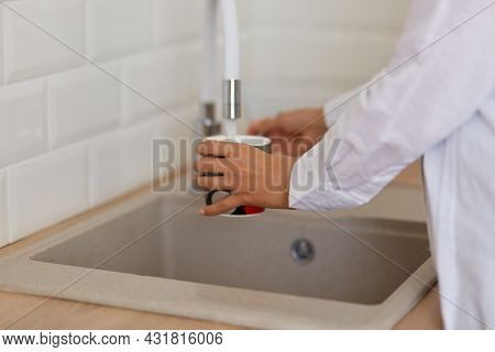 Human Hand Holding Cup Pouring Fresh Water At Kitchen Faucet, Wants To Drink Fresh Water Or Washing