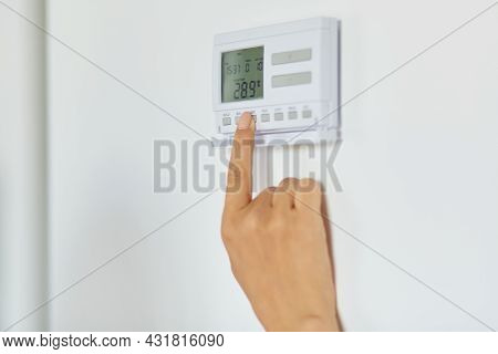 Close Up Shot Of Woman Hand Regulating Heating Temperature With Wireless Thermostat On The White Wal