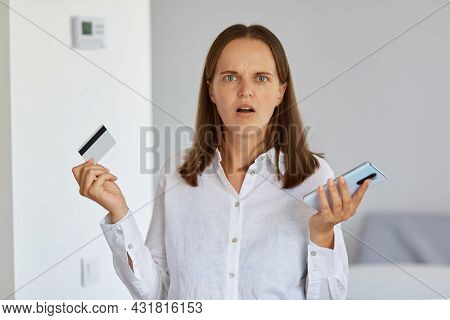 Portrait Of Scared Astonished Female Wearing White Shirt, Standing In Light Room, Holding Credit Car