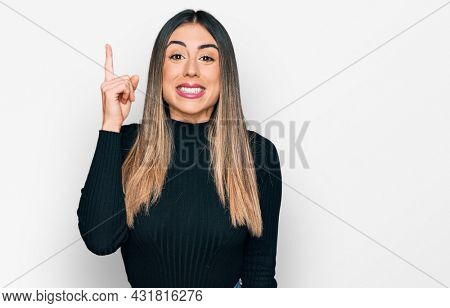 Young hispanic woman wearing casual clothes pointing finger up with successful idea. exited and happy. number one.