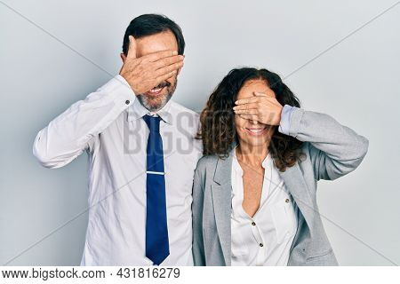 Middle age couple of hispanic woman and man wearing business office uniform smiling and laughing with hand on face covering eyes for surprise. blind concept.