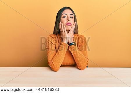 Young hispanic woman wearing casual clothes sitting on the table tired hands covering face, depression and sadness, upset and irritated for problem