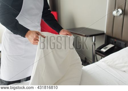 Partial View Of Housekeeper In Apron Changing Bedding In Hotel Room