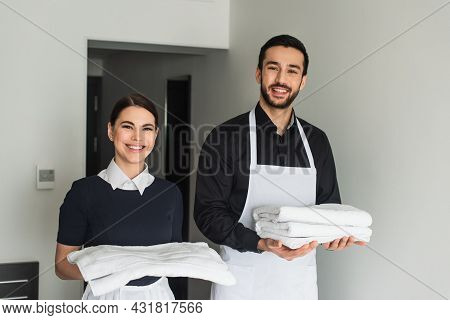 Smiling Housekeepers Holding White Bed Sheets And Towels In Hotel Room