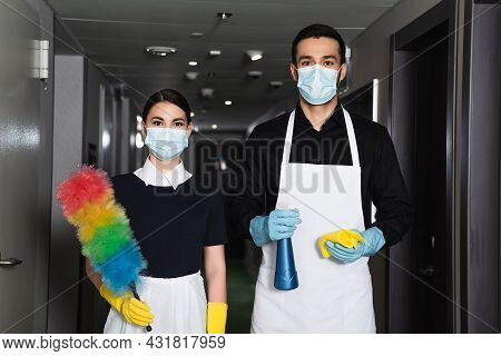 Housekeepers In Medical Masks And Rubber Gloves Holding Spray Bottle With Rag And Dust Brush