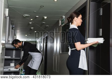 Young Maid In Uniform Holding Clean Bed Sheets Near Blurred Colleague Near Housekeeping Cart