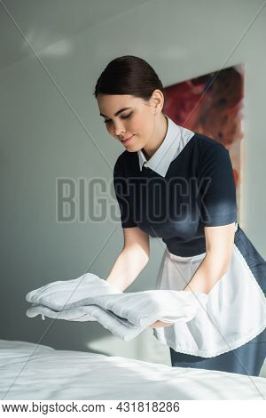 Cheerful Chambermaid In Uniform Putting Fresh Towels On Bed In Hotel Room
