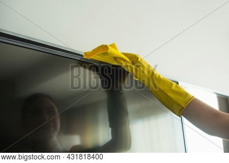 Cropped View Of Housekeeper In Rubber Glove Cleaning Tv Display With Rag