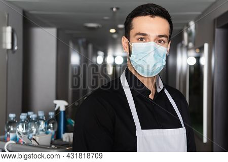 Housekeeper In Apron And Medical Mask Looking At Camera In Corridor Of Hotel