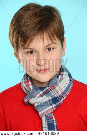Close-up Portrait Of A Trendy, Cheerful Teenage Boy Wearing A Red Sweater And Plaid Scarf. He Looks