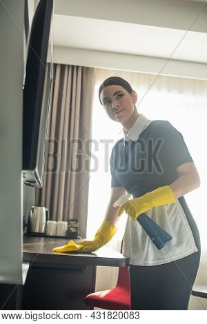 Young Maid In Rubber Gloves Cleaning Wooden Surface With Rag