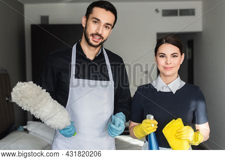 Happy Housekeepers Looking At Camera While Holding Cleaning Supplies