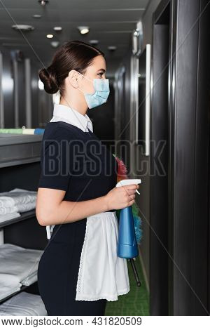 Side View Of Young Maid In Uniform And Medical Mask Holding Spray Bottle Near Blurred Housekeeping C