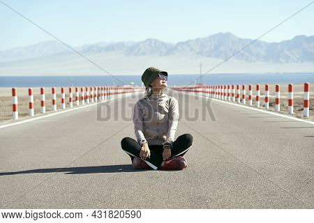 Asian Woman Tourist Sitting In The Middle Of An Empty Open Road Looking At View With Lake And Rollin