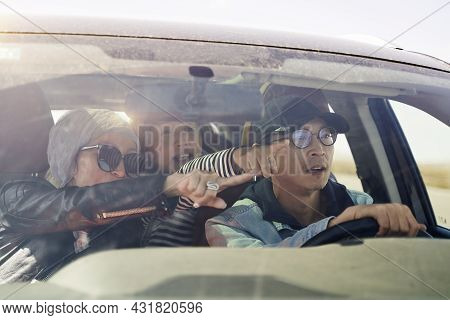 Group Of Happy Asian Friends Enjoying A Sightseeing Trip By Car