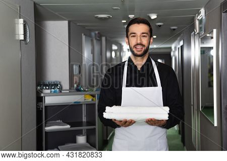 Smiling And Bearded Housekeeper Holding White Clean Bed Sheets