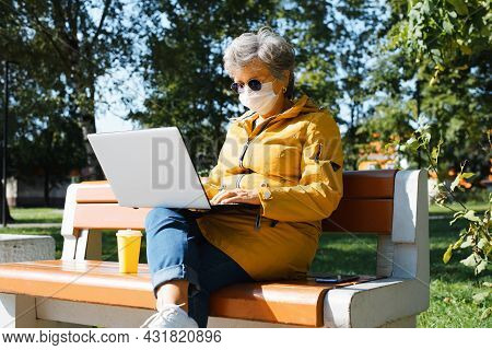 Senior Woman In Glasses And Protective Face Mask Works On Laptop Online, Retired Freelasner Working