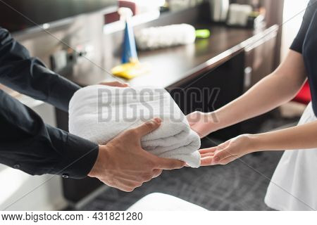 Cropped View Of Housekeeper Giving Clean White Towels To Maid In Hotel Room