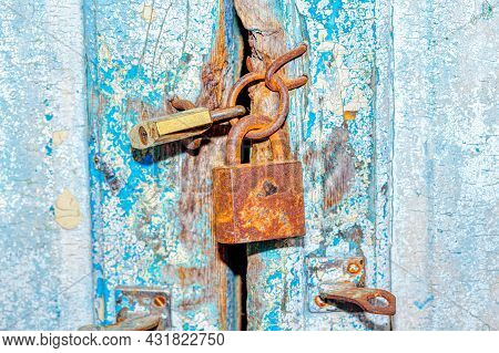 Old Rusty Locks Of Old House . Closed Wooden Door Of Abandoned House