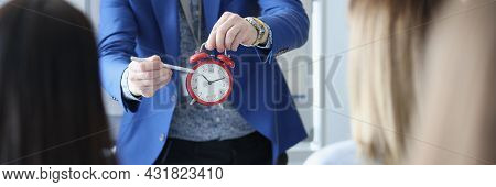 Business Coach Showing Listeners Time On Red Alarm Clock Closeup