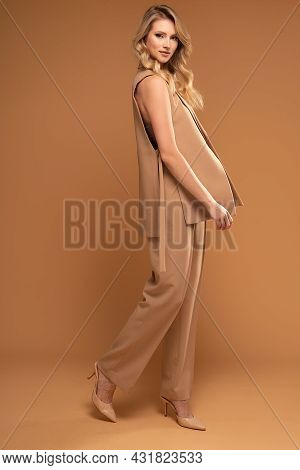 Fashion Studio Shot Of A Blonde Model Woman In A Suit Isolated At The Brown Studio Background. Young