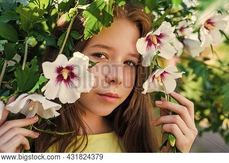 Happy Childhood. Cheerful Pretty Child At Blooming Tree Outdoor. Vacation Time. Summer Fashion And B