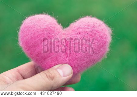 Pink Woolen Heart Being Held By Fingers On The Green Nature Background