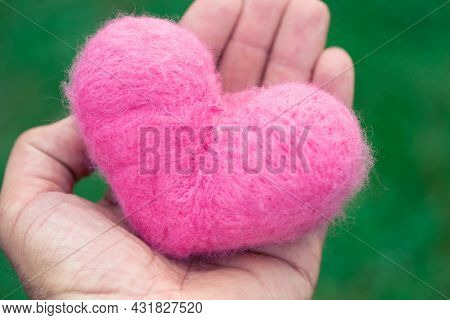 Pink Woolen Heart Lying In A Hand On The Green Nature Background