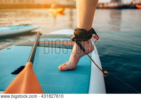 Close Up Of Female Legs Standing On Blue Yellow Color Sup Stand Up Paddle Board Or Surfboard Puts On