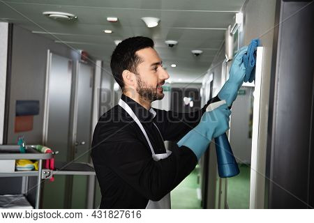 Side View Of Cheerful And Bearded Housekeeper In Rubber Gloves Cleaning Mirror In Corridor Of Hotel