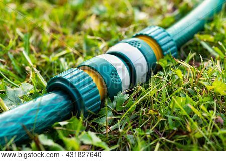 Garden Irrigation Hoses Connected With A Modern Plastic Hose Connector For Quick Connection Lying On