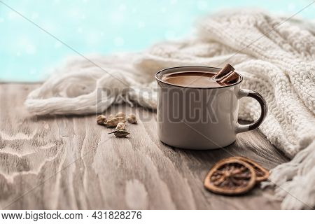 A Mug Of Hot Chocolate Or Cocoa With Cinnamon Sticks On A Wooden Table. Warm Scarf And Cozy Autumn